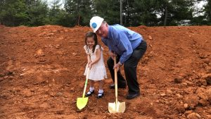 Mr. Smith and his granddaughter breaking ground.