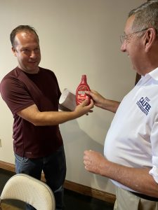 Steve Eimers presenting Rep. Kent Calfee with Strawberry Hershey's Syrup