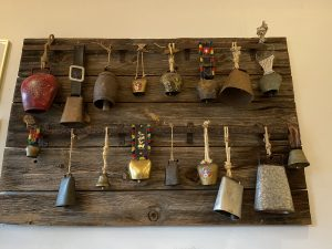 a collection of cow bells hanging up inside the pizza barn
